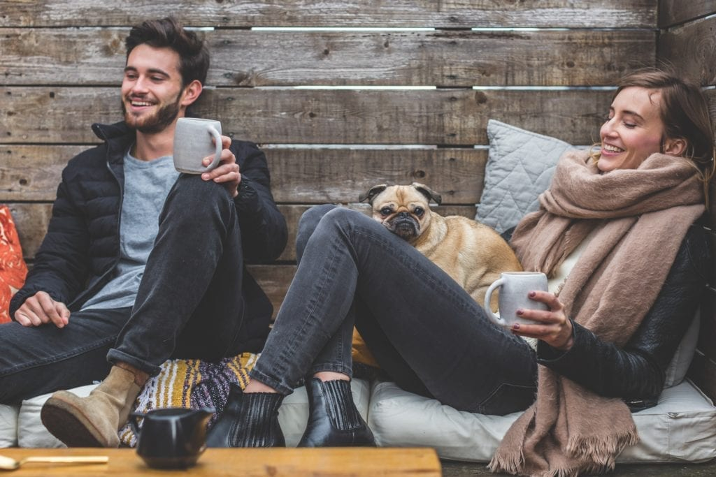 A couple relaxes in a cabin with their pug, just after visiting Alaska Dental Arts